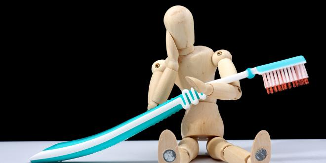 a wooden figure with a toothache and a giant brush